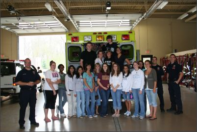 High School students posed with firefighters at the fire station.
