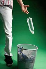 Man Throwing Plastic Bottle in Trash Can
