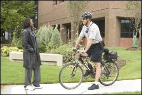 Officer on bike talking with woman.