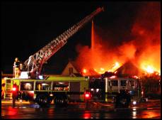 Ladder truck fighting a fire at night.